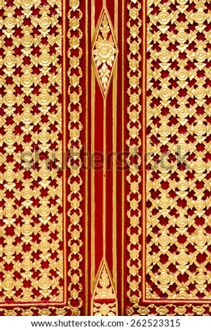 Traditional Thai style wood-carved temple door with red and gold pattern - stock photo