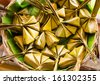 """Traditional Thai sweet food, steamed rice dough with sweet coconut stuffing in banana leaf . also called """"ka-nom-sai-sa i"""" on wicker basket in culture market at Thailand - stock photo"""