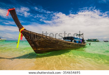 Traditional Thai wooden longtail boats with decorative sash ribbons moored in crystal waters on the shore of Bamboo Island near Krabi