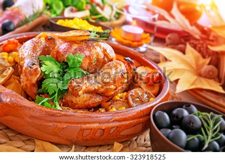 Traditional Thanksgiving day dinner, tasty roasted turkey, cold cuts, corn and olives on the festive table decorated with dry maple leaves and candles - stock photo