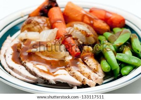 traditional Thanksgiving or Christmas turkey dinner with crispy skin, turkey slices and fresh roasted  vegetables smothered in gravy - stock photo