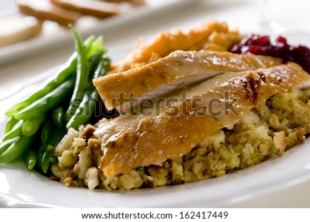 Traditional Thanksgiving turkey dinner with cranberry sauce, stuffing, green beans and sweet potato casserole. - stock photo