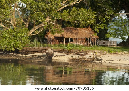 traditional thatch hut in Kwato, Milne Bay, Papua New Guinea typical of houses and living conditions throughout PNG - stock photo