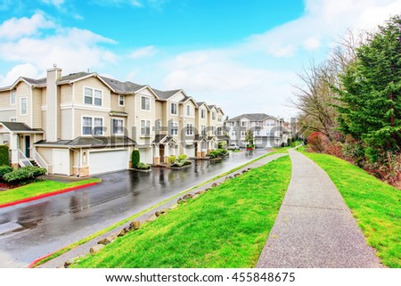 Traditional town house with small garage. Concrete walkway - stock photo