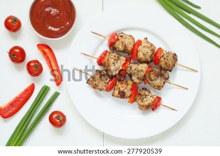 Traditional turkey kebab skewer barbecue meat with vegetables and sauce on white dish. Served on kitchen table background. Rustic style, natural light. - stock photo