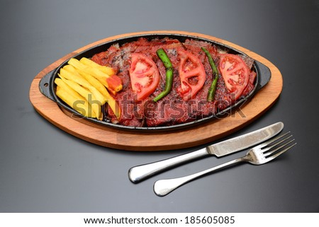 Traditional Turkish Bursa iskender kebap doner served with special red sauce and yogurt in the middle, garnished with grilled tomatoes and peppers - stock photo