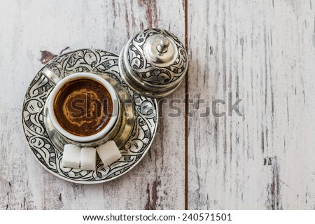Traditional Turkish coffee in traditional silver cup on white wooden table  - stock photo