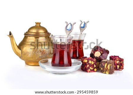 Traditional turkish delight rahat lokum with two glasses of tea and teapot on a white background - stock photo