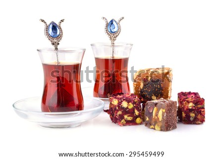 Traditional turkish delight rahat lokum with two glasses of tea on a white background - stock photo