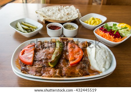 traditional turkish iskender kebab with garniture on a wooden surface at restaurant - stock photo