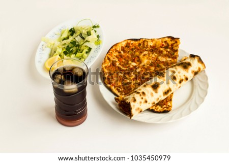 Traditional Turkish pizza,Lahmacun rolled on the round porcelain plate with cold drink and vegetables garniture.White ground,close up taken,isolated.