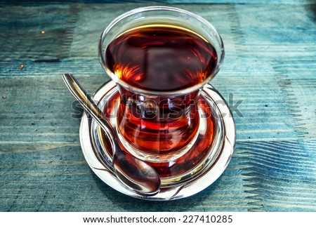 Traditional Turkish tea in glass on blue background - stock photo