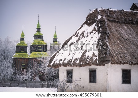 Traditional Ukrainian architecture. Old house with thatched roof and wooden church. Pirogovo museum, Kiev, Ukraine, Europe. The artistic style of photography processing. Color toning - stock photo