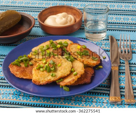 Traditional Ukrainian homemade potato pancakes and green spring onions with sour cream