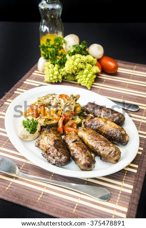 Traditional ukrainian meat rolls with buckwheat and minced meat stuffing, served with stuffed mushrooms and vegetable ragout