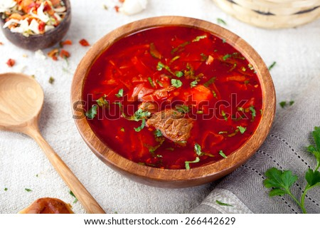 Traditional Ukrainian Russian vegetable soup, borsch with garlic donuts, pampushki on a white wooden background  - stock photo