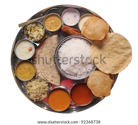 Traditional vegetarian indian thali lunch-  food and meals with rice, phulka(chapatti), puri(poori), curries, sambar, rasam, pulao, papad and sweets isolated on white. Complete nutritional indian food - stock photo