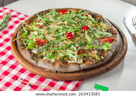 Traditional Vegetarian Italian pizza with vegetables, tomato sause,cheese, rocket salad and dried basil on the wooden plate close up - stock photo