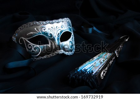 Traditional veneztan carnival mask and a fan - stock photo