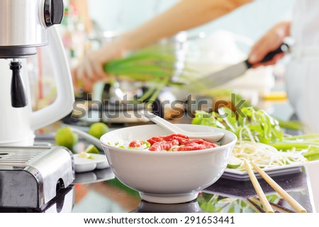 Traditional Vietnamese beef noodle soup Pho Bo with garnish of leaves of cilantro, Asian basil and bean sprouts on kitchen table. Young woman is cooking in background. Healthy food. - stock photo