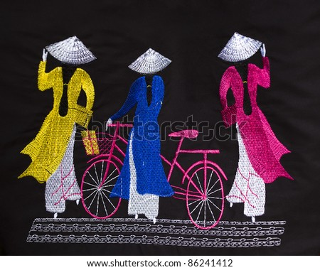 traditional Vietnamese particulars i.e. Ao Dai, hat and bicycle embroidered on a cloth as souvenir available for sale