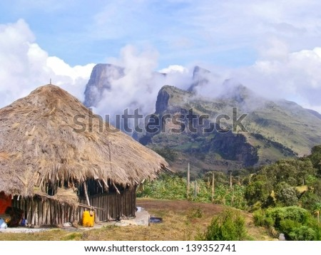 Traditional village house in misty mountains. Shot in Ethiopia. - stock photo