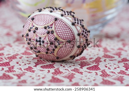 Traditional wax painted Easter egg  against a red and white lacy background - stock photo