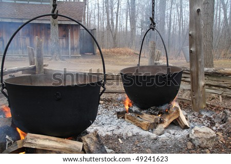 Traditional way of making maple syrup by boiling the sap in a cauldron  at sugar shack - stock photo