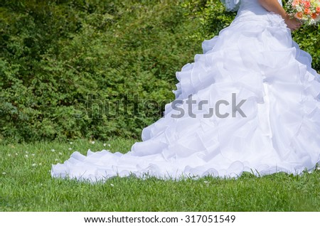 Traditional White Wedding Dress in the Green Summer Park Closeup