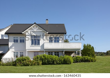 Traditional white wooden house in Norway, summer day
