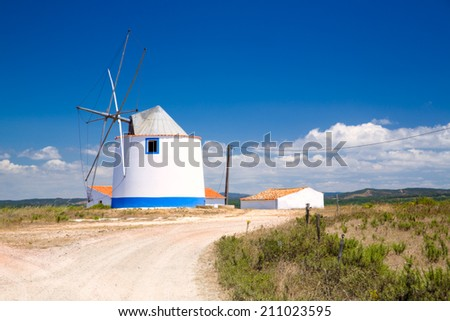 Traditional windmill in the Algarve, Portugal, with beautiful blue sky and white clouds, and two barns aside with red roofs - stock photo