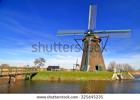Traditional windmill on a field near a canal in Kinderdijk, Holland
