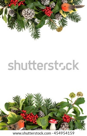 Traditional winter background border with holly, ivy, fly agaric mushroom and robin decorations with snow covered pine cones and fir over white. - stock photo