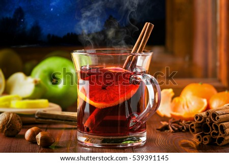 Traditional winter holiday alcoholic drink. Mulled wine with lemon slice on a table. Starry night winter landscape in a window.