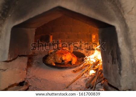 Traditional wood fired oven in the Andes region of Ecuador with flames and sticks with chicken cooking