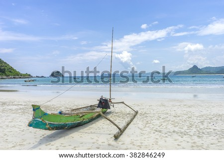 Traditional wooden boat park at sea shore with cloudy skies at South Lombok island, Indonesia - stock photo