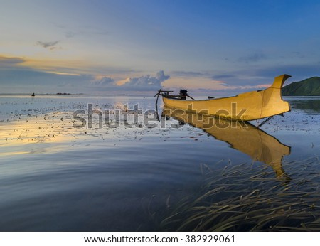 Traditional wooden boat with sunrise reflection - stock photo