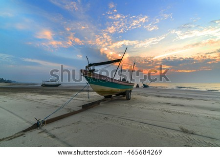 Traditional wooden boat with sunrise skies background