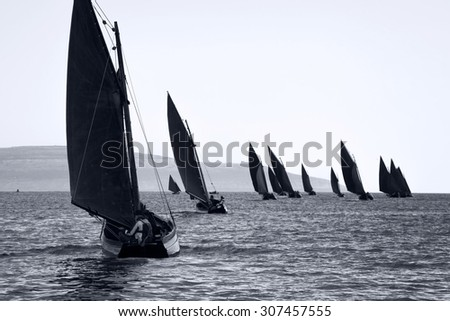 Traditional wooden boats Galway Hooker, with red sail, compete in regatta. Ireland.