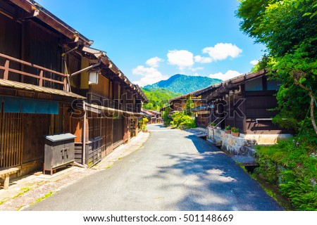 Traditional wooden buildings line the sides of the main street of Tsumago, an old post town on the ancient Nakasendo route during Edo period in Japan. Horizontal