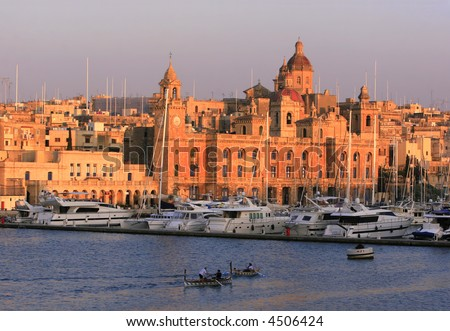 "Traditional wooden Dghajsa boats against the backdrop of Vittoriosa Wharf and the buildings of Vittoriosa, one of the ""Three Cities"" of Malta, during sunset"