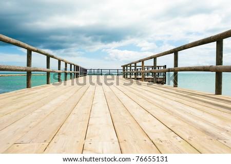 Traditional wooden footbridge  facing  a dramatic ocean setting - stock photo