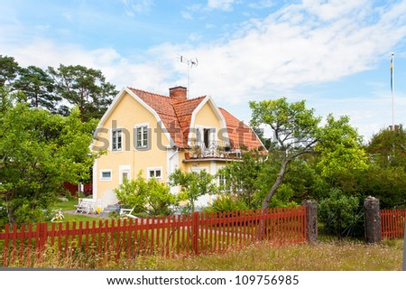 Traditional wooden house in south-eastern Sweden, painted in yellow - stock photo