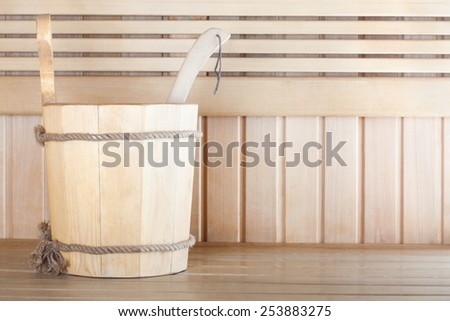 Traditional wooden sauna for relaxation with bucket of water  - stock photo