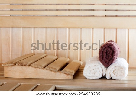 Traditional wooden sauna for relaxation with set of clean towels - stock photo