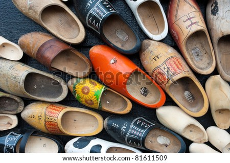 traditional wooden shoes in all sizes and colors hanging on a wall - stock photo