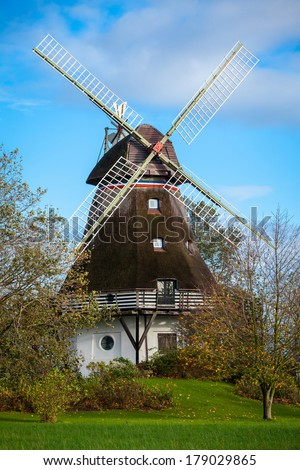 Traditional wooden windmill in a lush garden with four sails or blades turning in the wind to generate power and energy for farming or manufacture from the kinetic energy of the wind