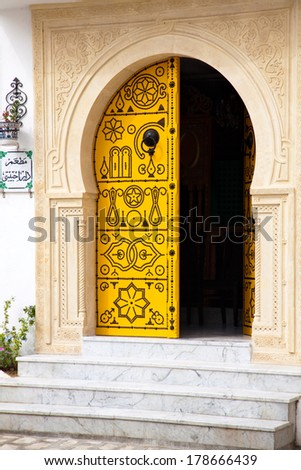 Traditional yellow door of Tunisia with black ornaments