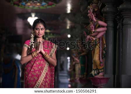traditional Young indian woman praying in the temple - stock photo