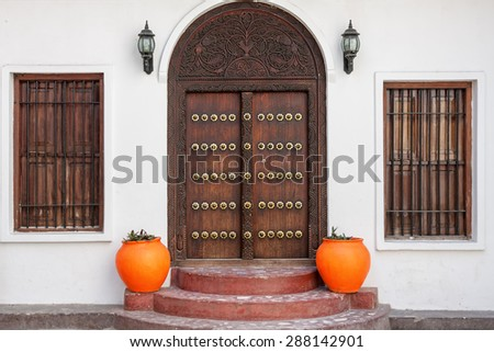 traditional zanzibar wooden door and doorway ornately carved and decorated with pots - stock photo